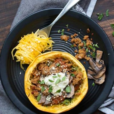 Baked spaghetti squash bowl with toppings on a black plate