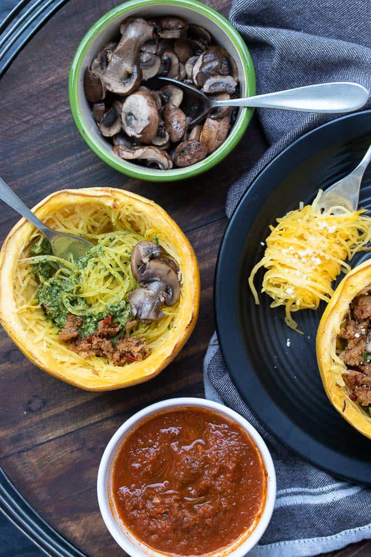 Baked spaghetti squash half being topped with mushrooms, marinara and pesto