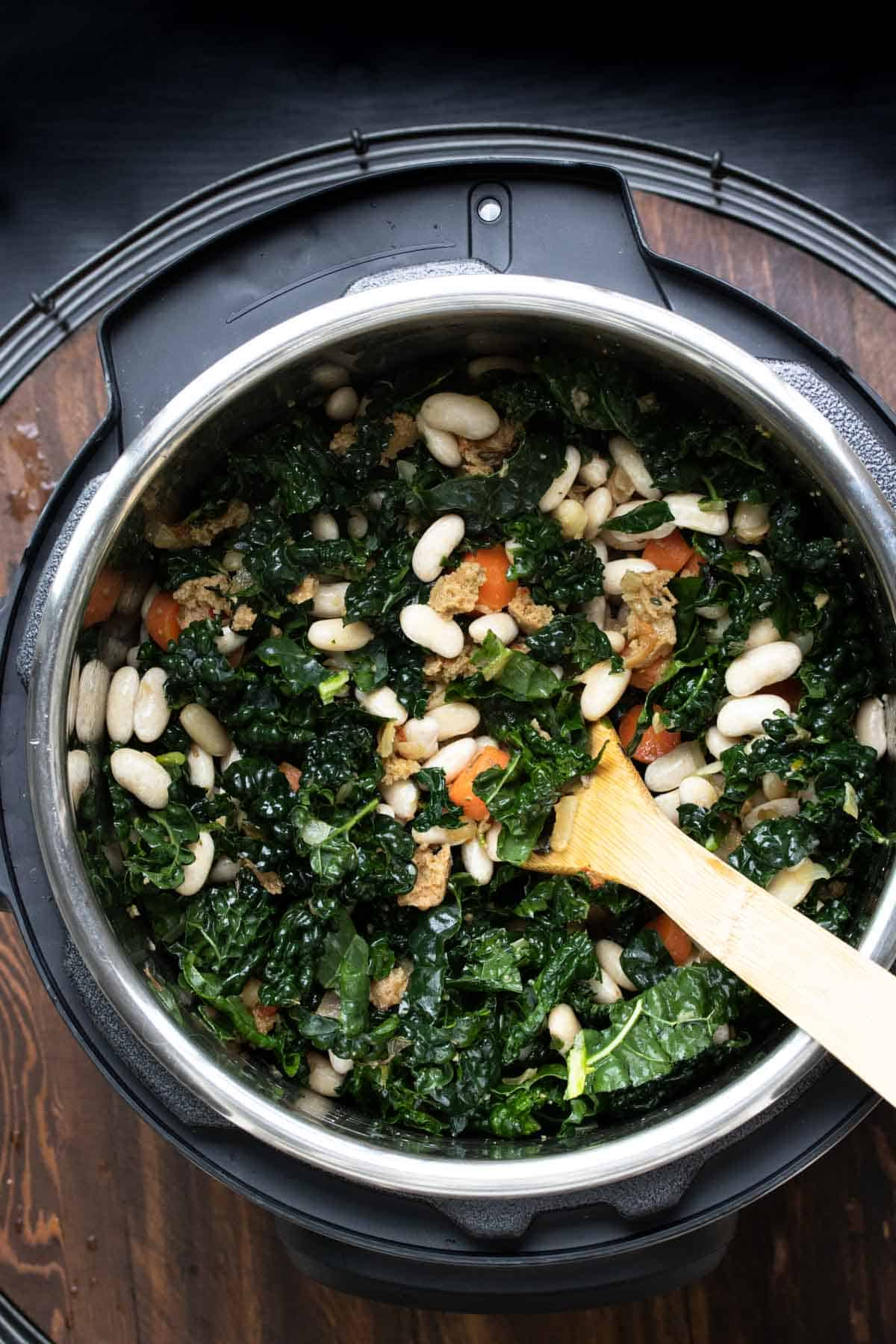Top view of kale, white beans, carrots and sausage being mixed in an instant pot