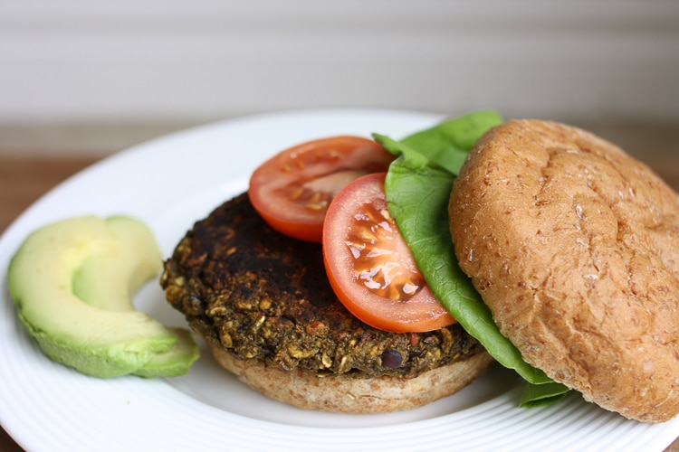 An open veggie bean burger topped with tomato and lettuce