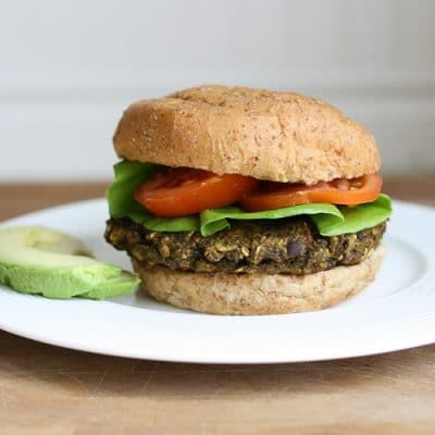 A veggie bean burger on a bun with salad