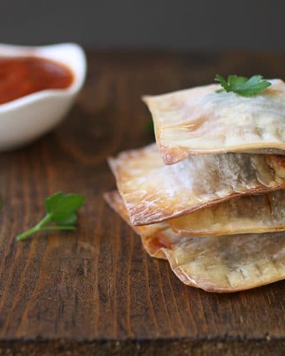 A stack of lasagna wontons on a wooden surface next to dipping sauce