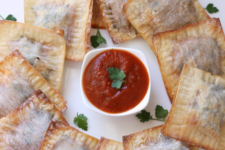 Lasagna wontons on a white plate with red dipping sauce in the middle