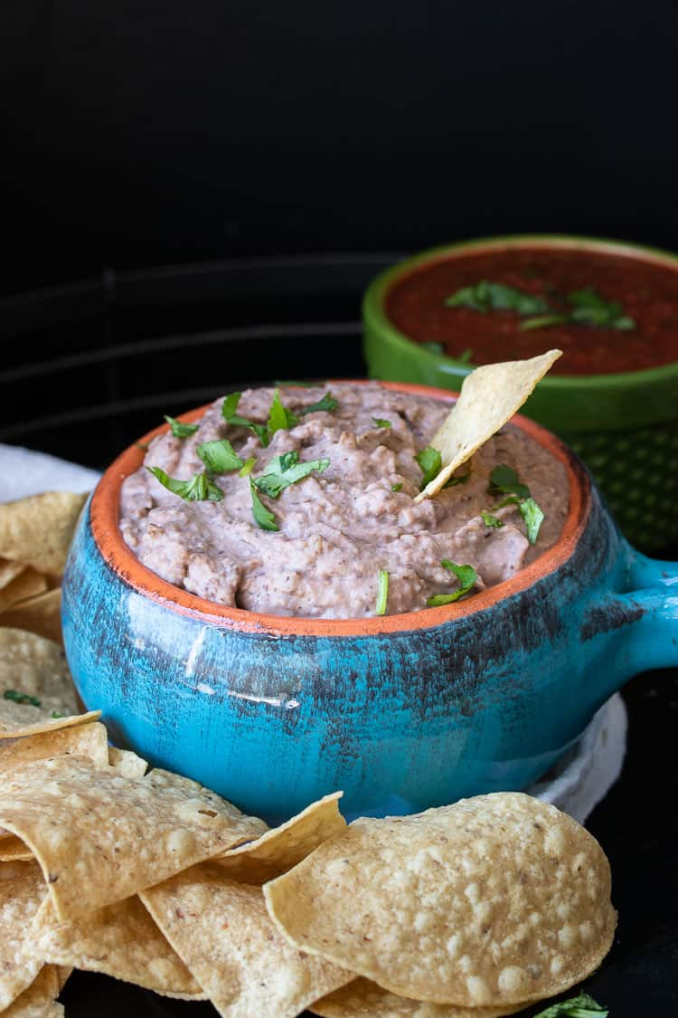 Turquoise bowl with chip dipping in bean dip