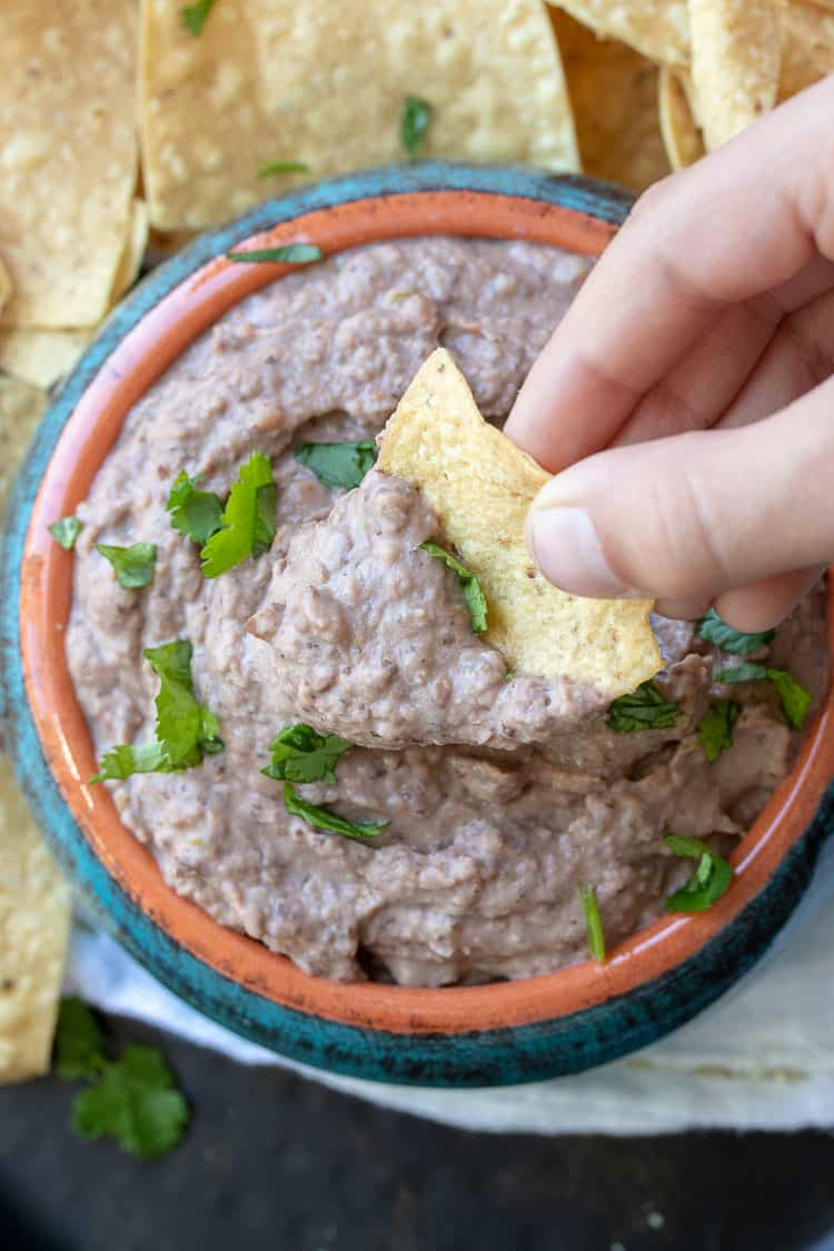 Hand dipping chip into bean dip in a turquoise bowl