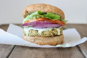 A Cauliflower burger topped with onion, tomato and salad in a burger bun