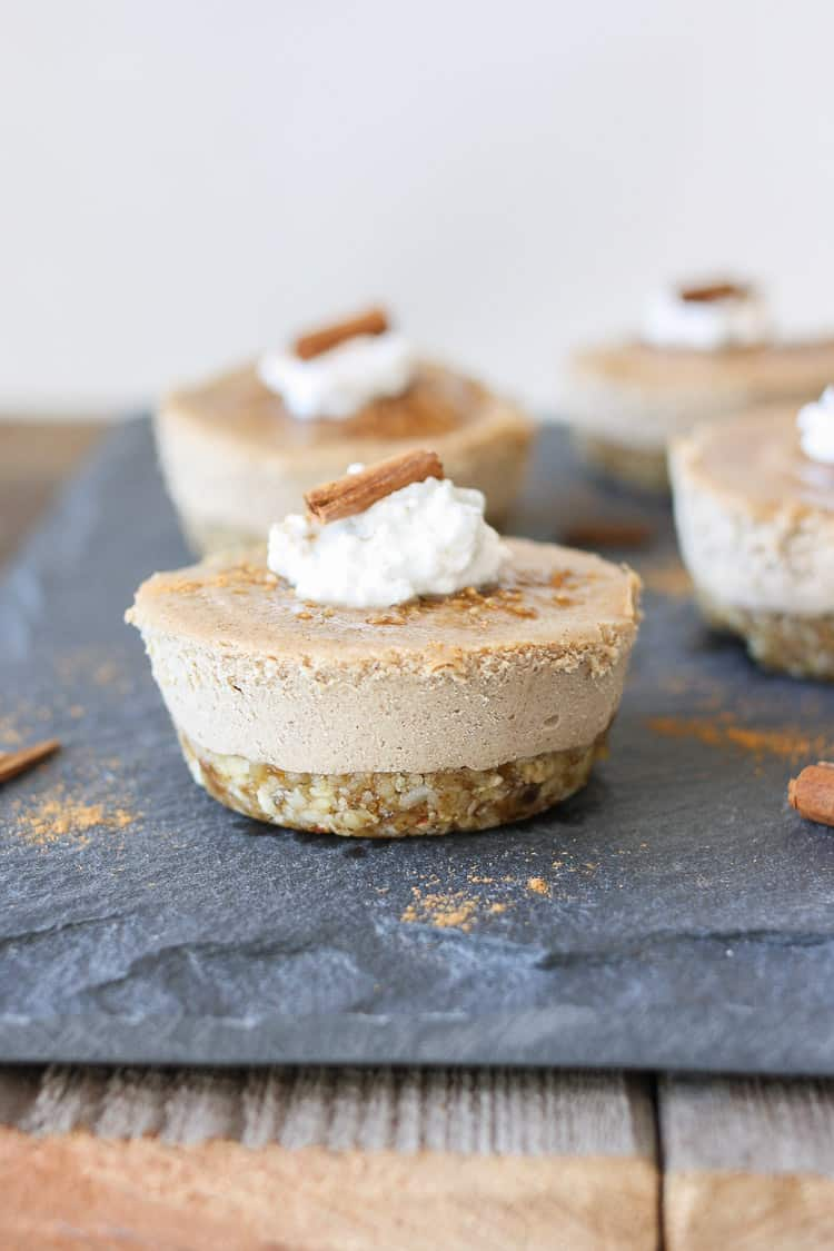 Raw vegan churro cheesecake cups sitting on a slate surface