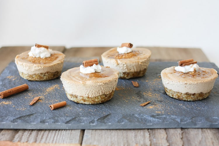 Raw vegan churro cheesecake cups topped with coconut cream and cinnamon sticks