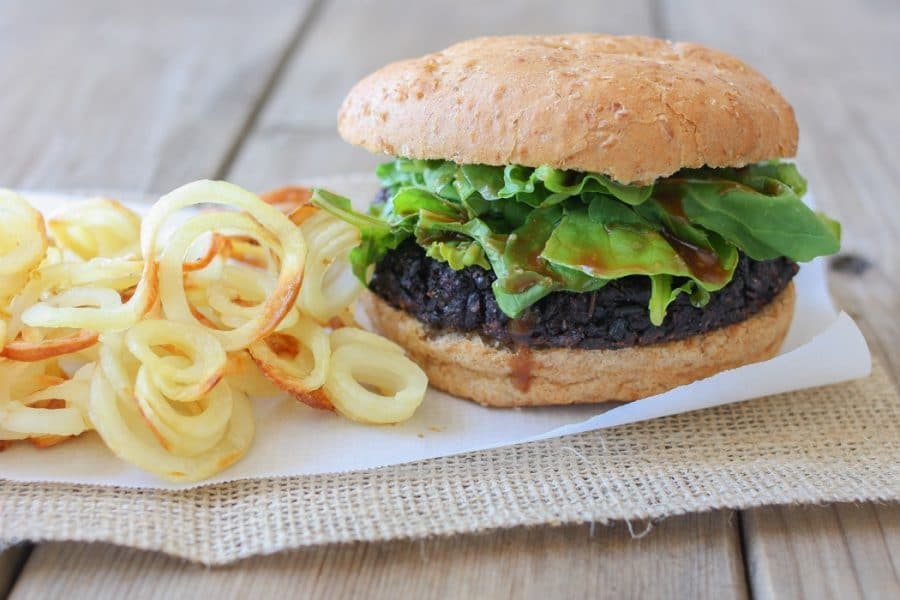 A close up of a black rice burger on a bun
