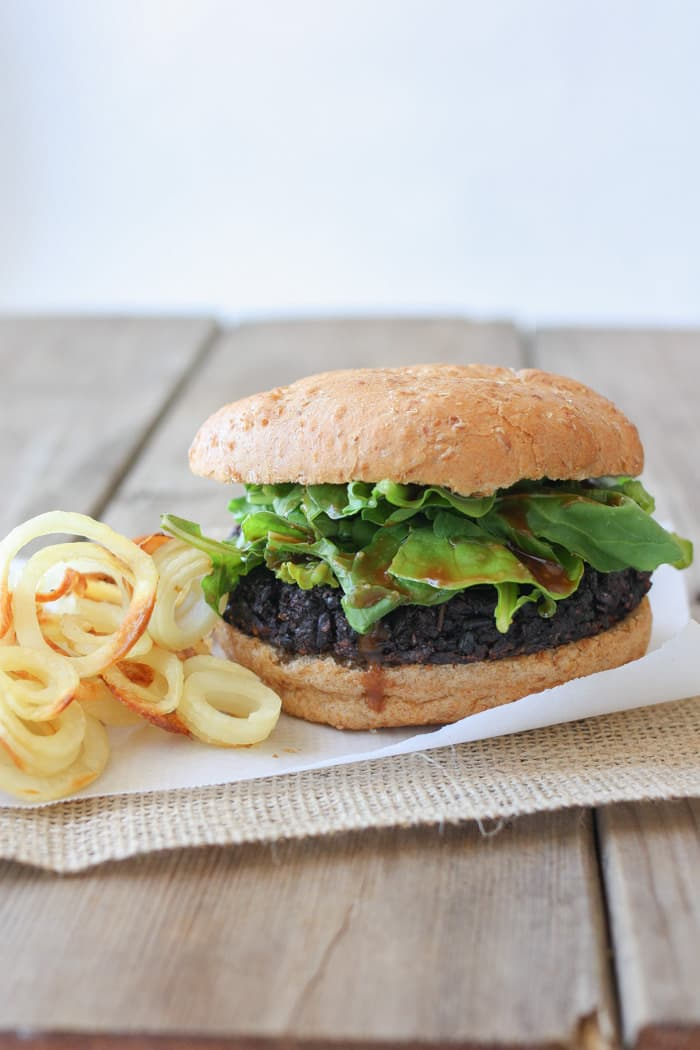 Black rice burgers on a bun with lettuce and onion rings at the side