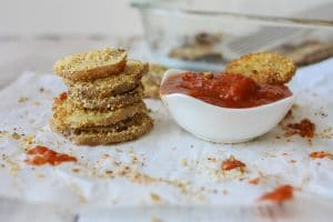 A stack of Hemp Almond Parmesan Potato Chip Rounds on parchment paper with a tomato dipping sauce