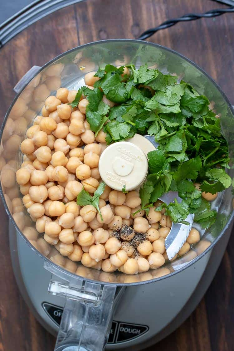 Food processor filled with chickpeas and parsley