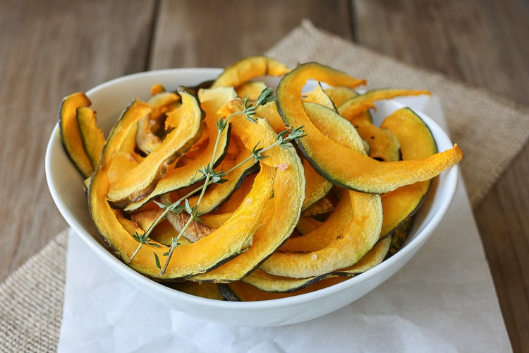 A close up of Baked Kabocha squash chips with thyme in a white bowl