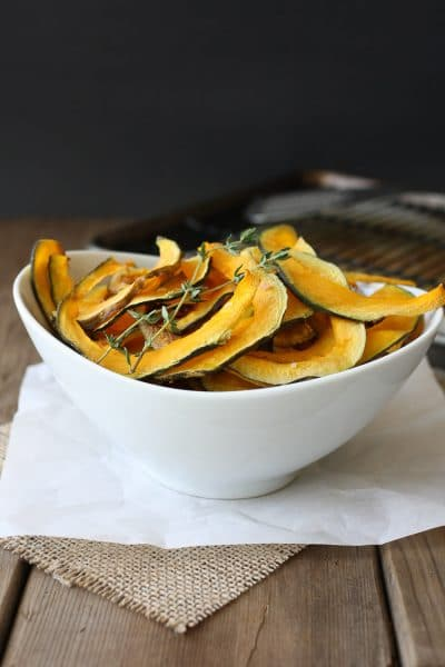 Baked Kabocha squash chips with thyme in a white bowl sitting on a wooden surface