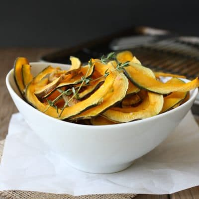 Baked Kabocha squash chips with thyme in a white bowl