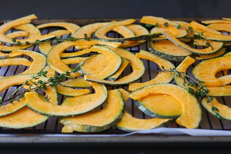 Slices of Baked Kabocha chips with thyme on a cooling rack