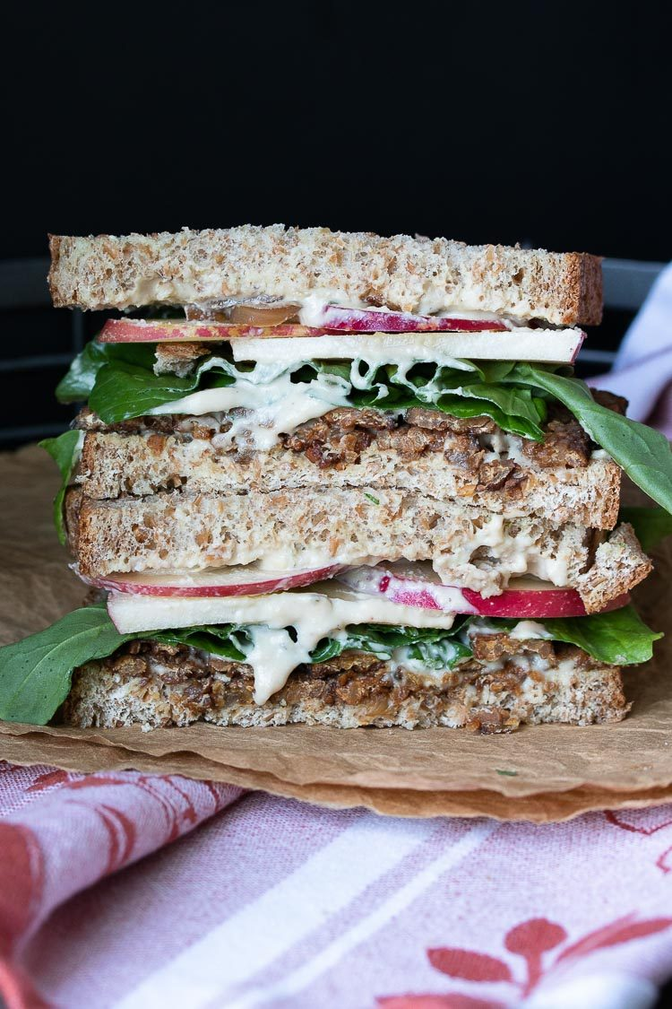 Front view of vegan tempeh bacon, apple, arugula sandwich on brown crumpled paper