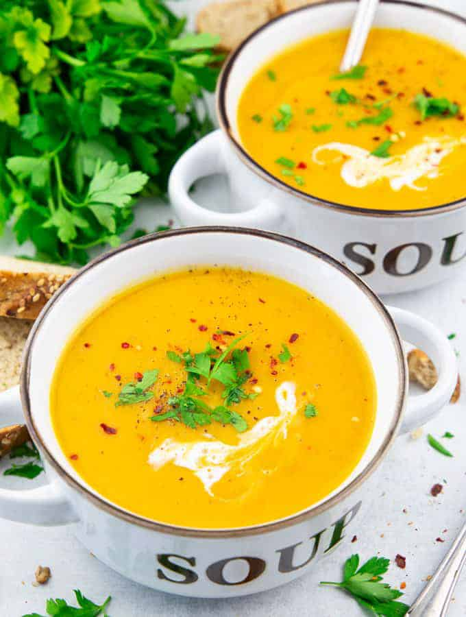 Two white soup bowls filled with creamy pumpkin soup