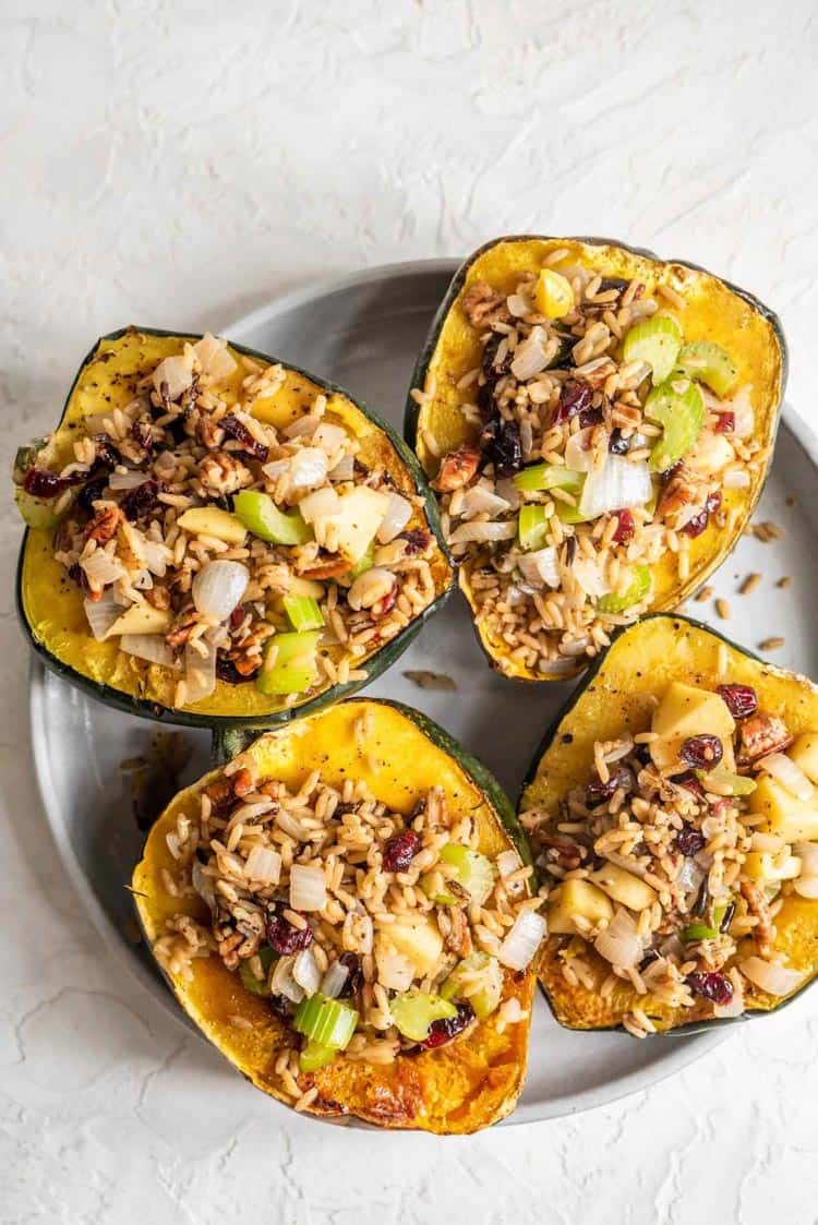 Plate of acorn squash cut in half and stuffed with a rice mixture