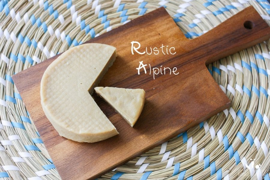 A photo of rustic alpine Miyoko's Creamery Vegan Cheese sitting on a wooden chopping board with a slice cut out