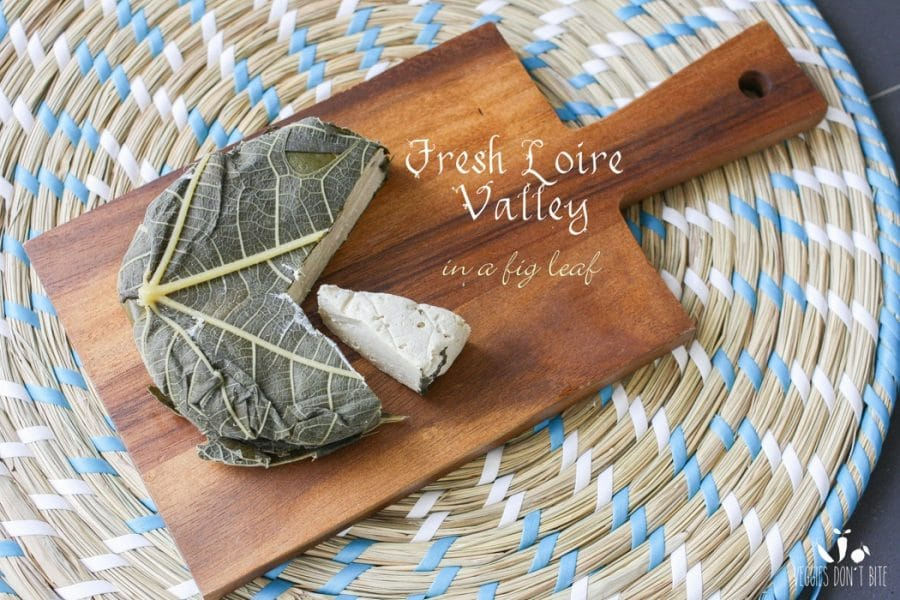 A photo of fresh loire valley Miyoko's Creamery Vegan Cheese wrapped in fig leaves sitting on a wooden chopping board