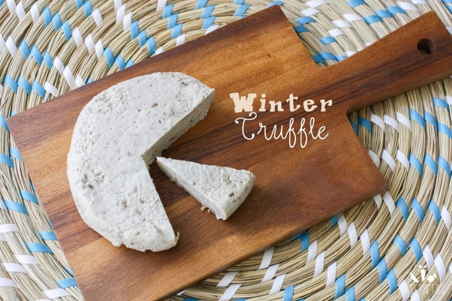 A winter truffle Miyoko's Creamery Vegan Cheese sitting on a wooden chopping board