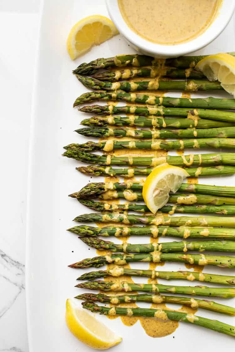 Asparagus on a white platter with lemon cream sauce drizzled over