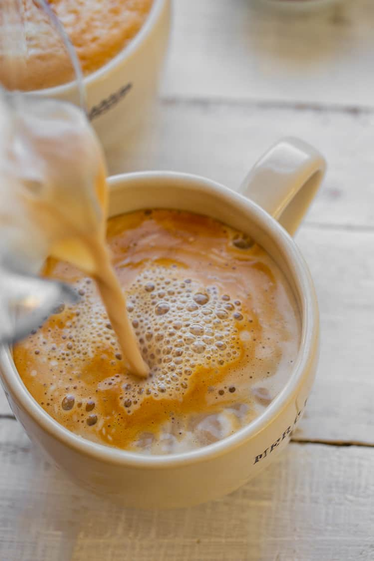 A cinnamon latte being poured into a mug