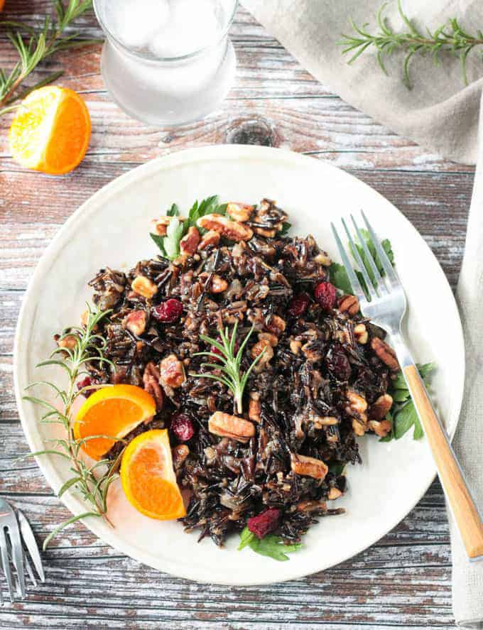 White plate filled with wild rice salad mixed with cranberries and pecans