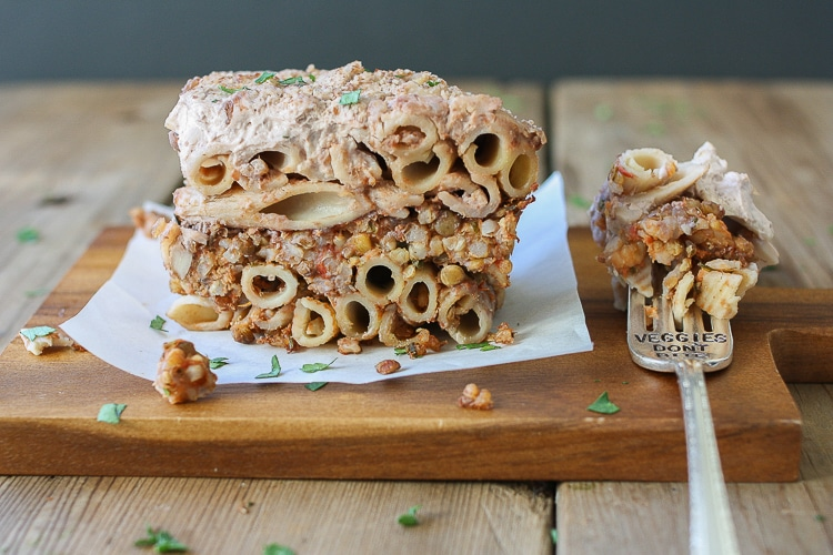 A side shot of vegan Greek Pastitsio on a wooden board with a fork