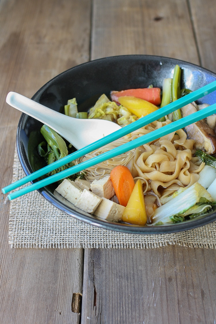 A closeup of a Vegan Japanese sukiyaki hot pot with blue chopsticks