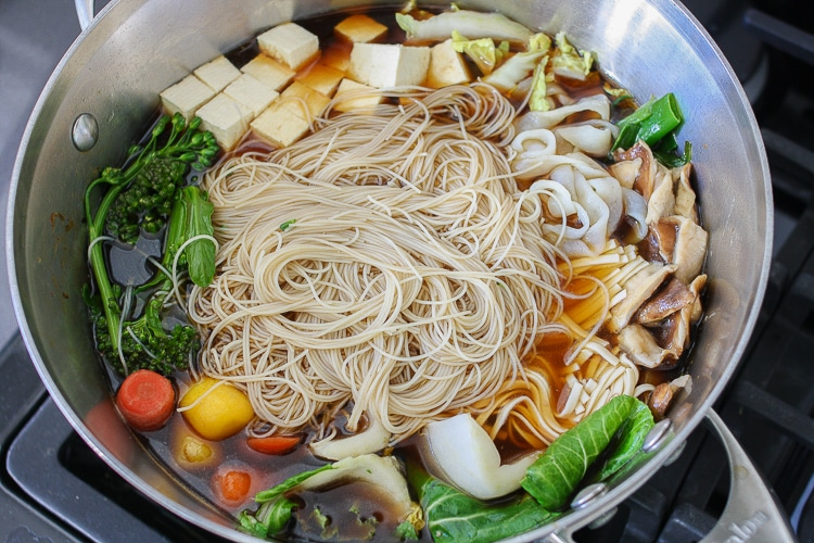 An overhead shot of all ingredients to make a vegan Sukiyaki Japanese hot pot in a large pan