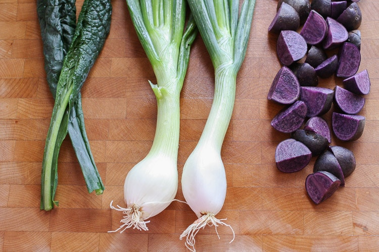 Leeks, chard and purple potatoes on a wooden board used to make a tahini power bowl