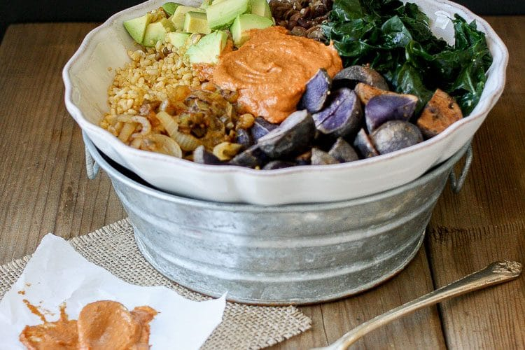 Barbecue Tahini power bowl with spinach, swiss chard or kale and potatoes sitting on a wooden surface with a fork