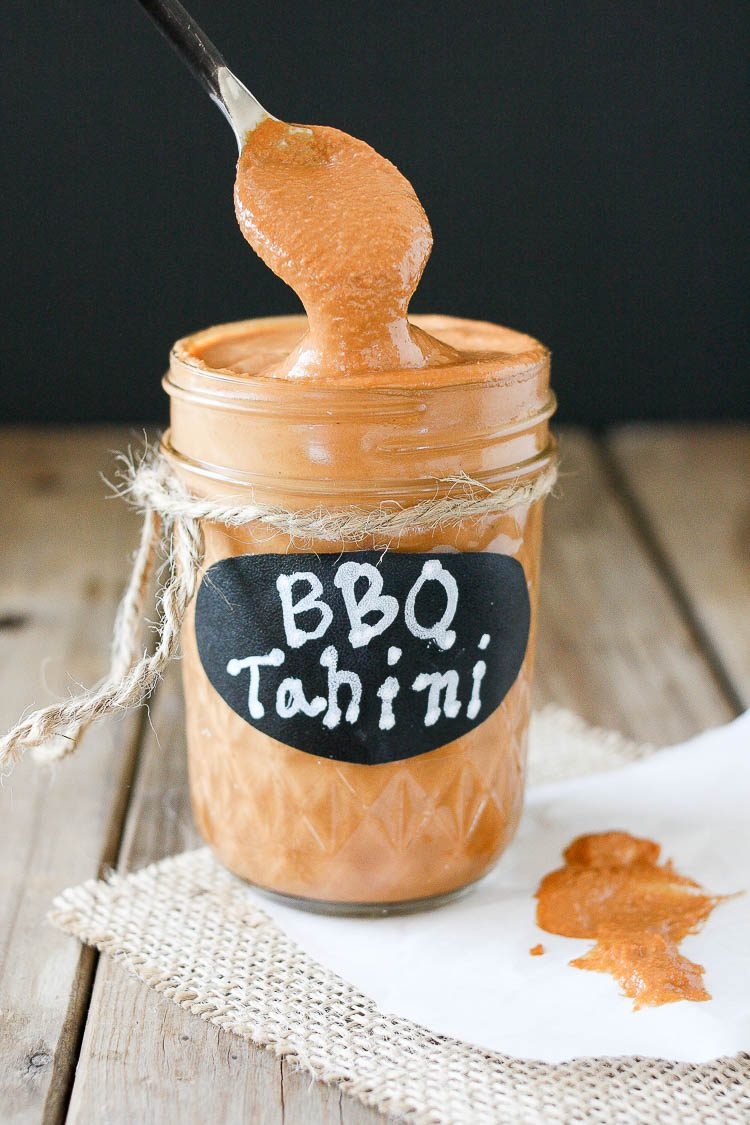 Barbecue tahini sauce in a glass jar with a spoon scooping some out of the jar