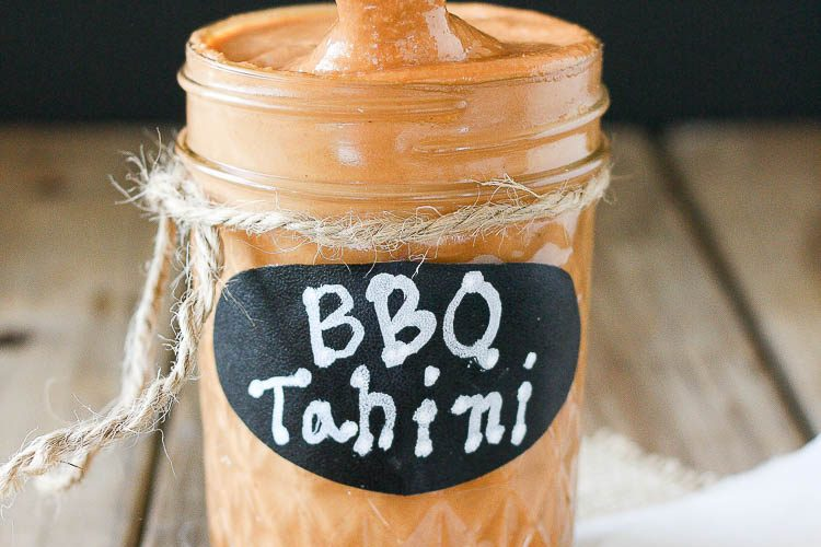 Barbecue tahini sauce in a glass jar sitting on a wooden surface