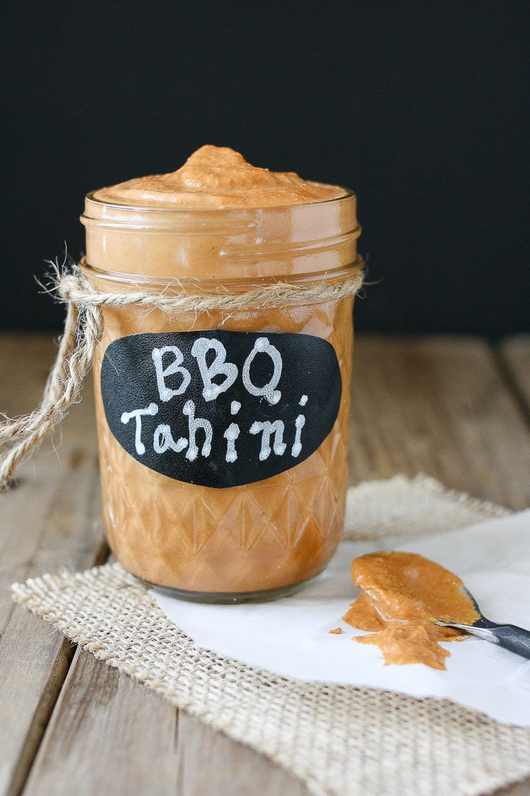 Barbecue tahini sauce in a glass jar with a black label with bbq tahini written