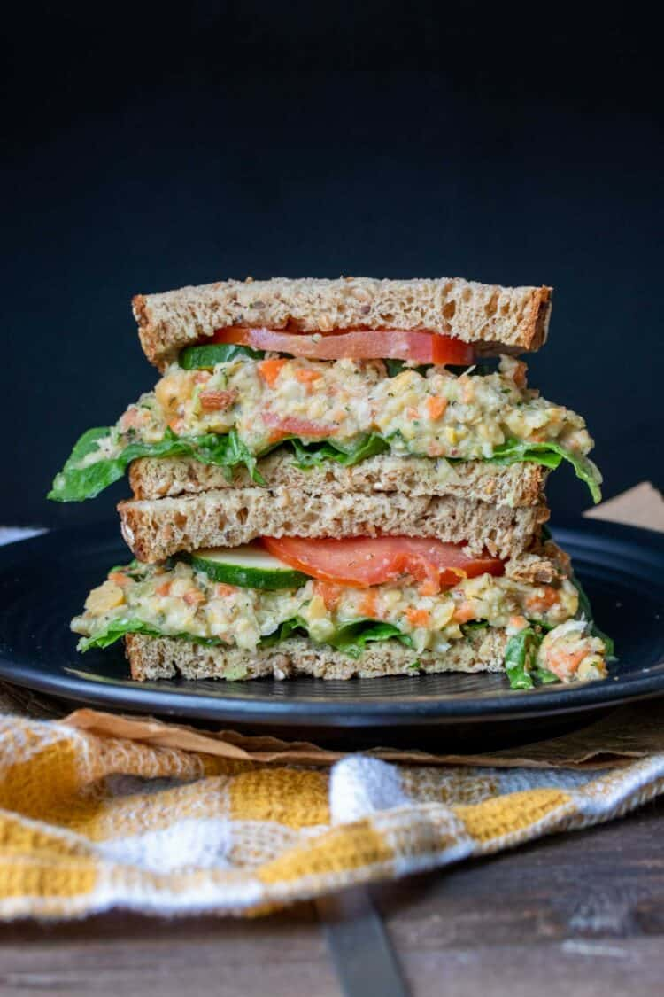 Mashed chickpea salad sandwich with veggies piled on a black plate