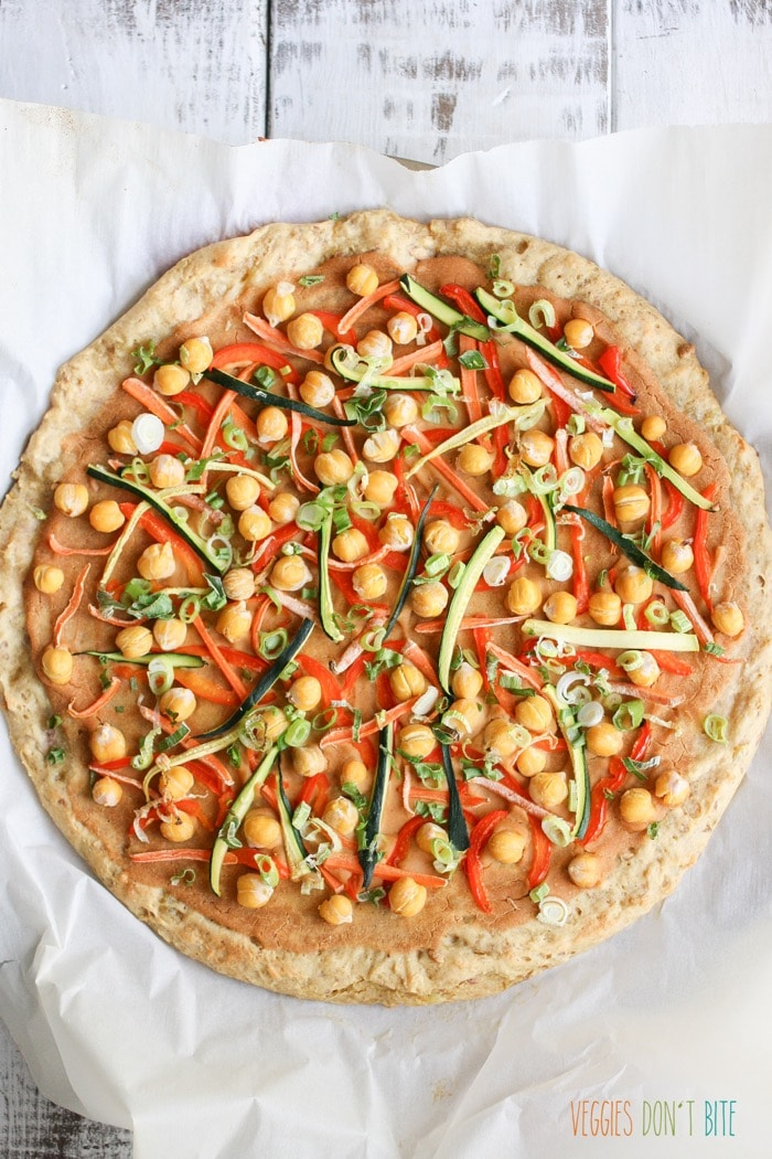 A baked Thai chickpea and veggie pizza on a white wooden surface
