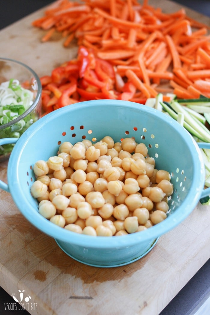 Chickpeas in a blue colander and other chopped vegetables in the background for making a veggie pizza