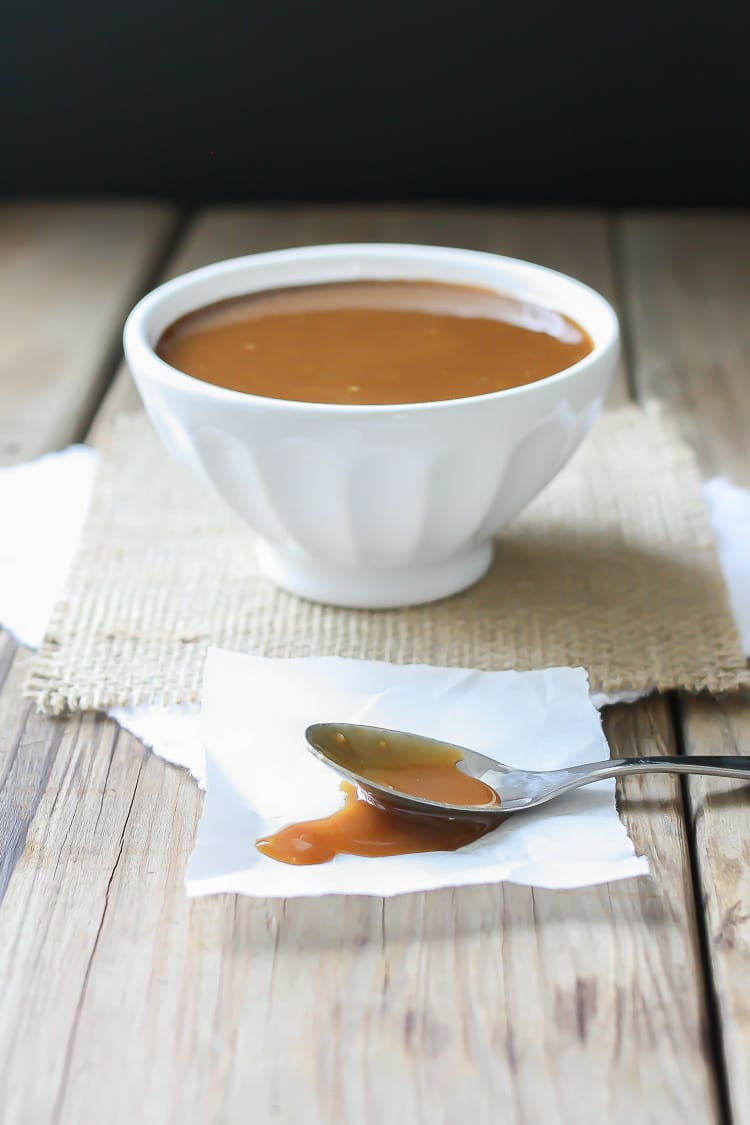 A side shot of Maple Miso Balsamic Sauce in a white bowl with a spoon at the side