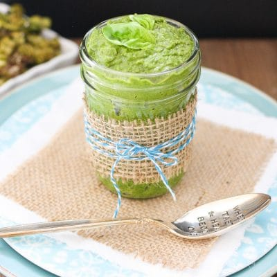 Vegan Spinach Pesto with Tahini in a glass jar with a spoon at the side