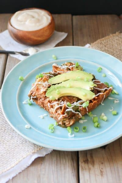 Vegan Enchilada Noodles Casserole on a blue plate topped with slices of avocado