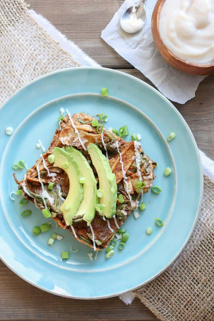 A slice of Enchilada Noodles casserole on a plate with avocado