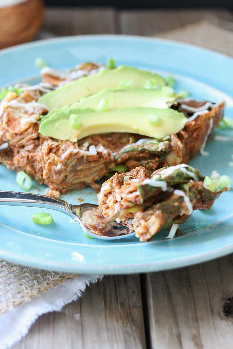 Enchilada Noodles casserole on a blue plate topped with avocado