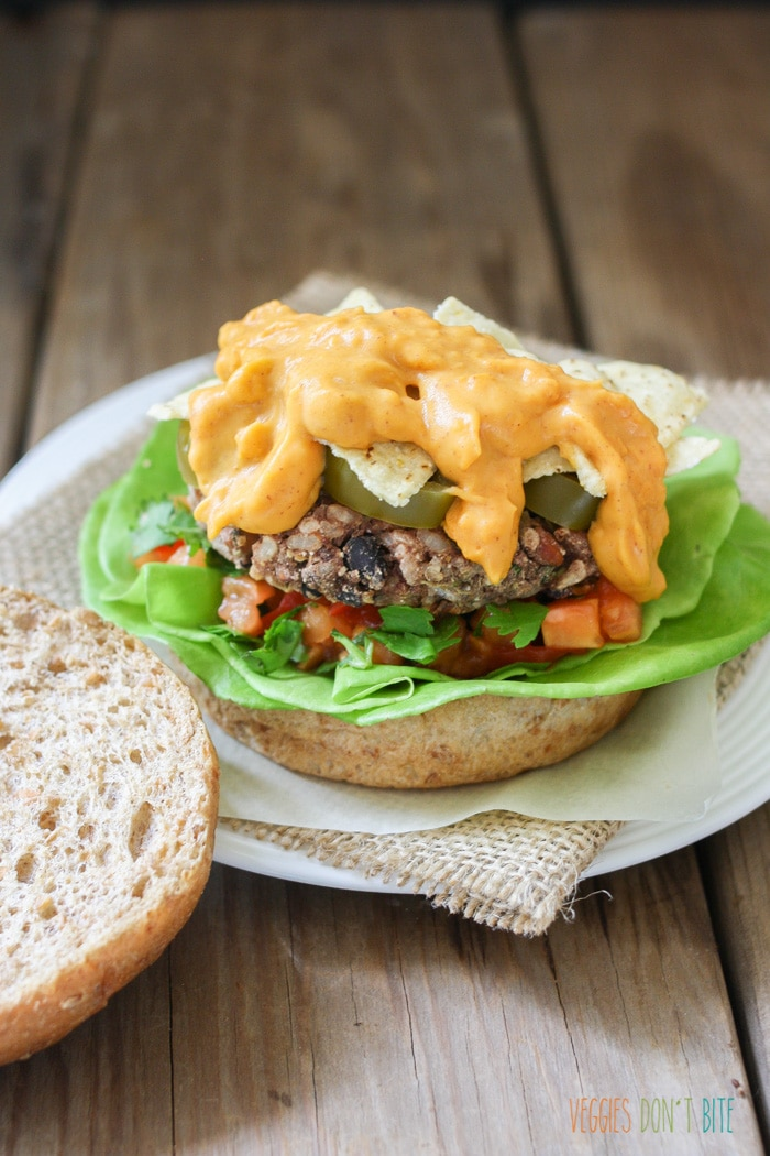 A close up of a Mexican nacho burger topped with vegan cheese sauce