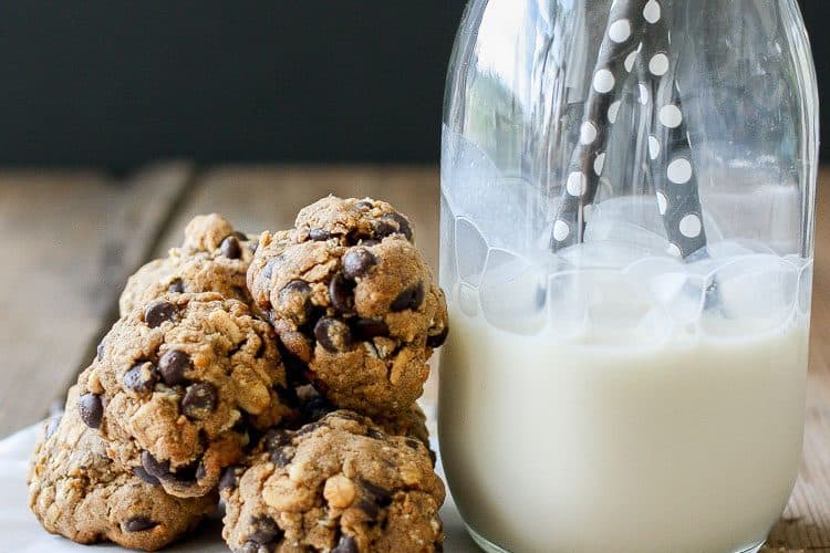 A small pile of Cookie Dough Balls‬‬‬‬‬‬‬‬‬‬‬ next to a glass of milk with straws