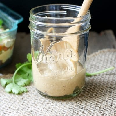 Creamy taco sauce in a jar with a wooden spoon