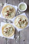 Top view of three crispy cauliflower tacos with cabbage, creamy dill sauce and hot sauce
