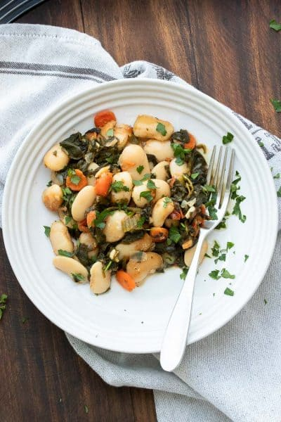 Baked lima beans and veggies on a white plate